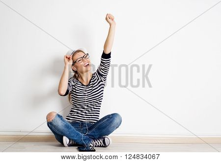 Happy female student relaxing at home, enjoying mp3 music in headphones. Young attractive woman singing song sitting on wooden floor in her room.