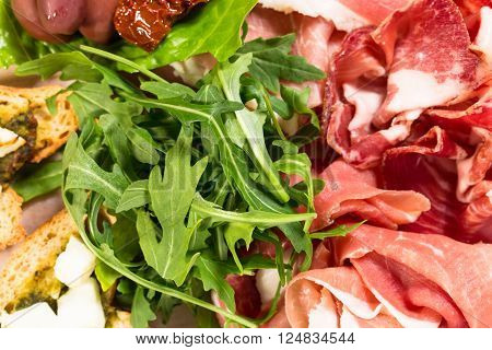 Traditional tuscan antipasto platter with cold cuts and fresh arugula. Macro shot. Photo can be used as a whole background.