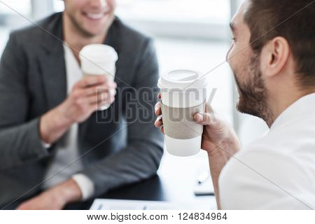 Get some rest.  Cheerful handsome  smiling nice colleagues sitting at the table and expressing positivity while drinking coffee