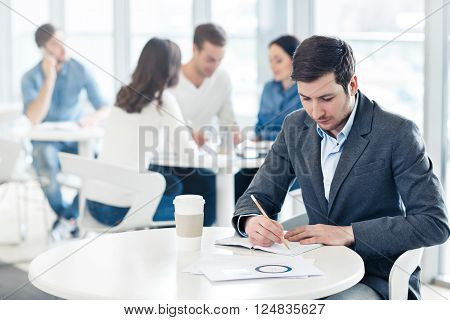 Have many plans.  Pleasant handsome man sitting at the table and making notes while his colleagues discussing the project