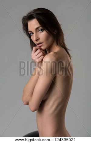 Beautiful slender Italian woman nude on gray
