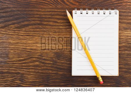 Set of notebook with yellow pencil on the wooden background