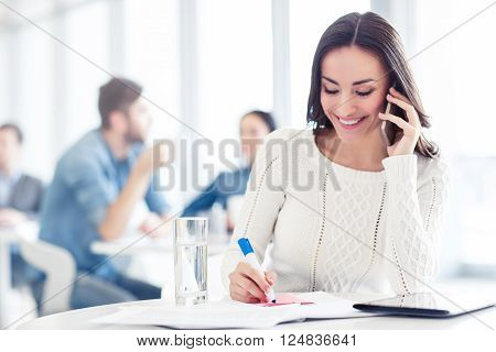 In pace with progress. Cheerful beautiful delighted smiling woman talking on cell phone and making notes while sitting at the table