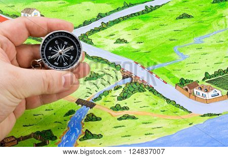 compass in hand and orientation on the map of the journey