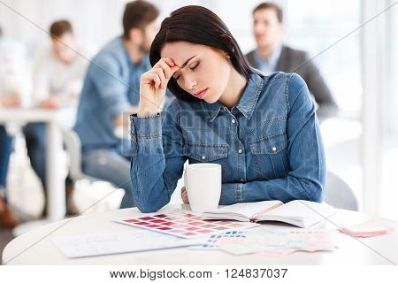 Felling tired. Cheerless beautiful girl holding her head and sitting at the table while feeling exhausted
