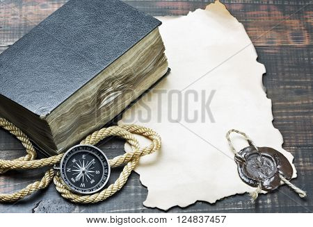 compass and an old book among other marine items