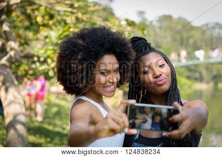 Brazilian afro women taking selfie photos in the park
