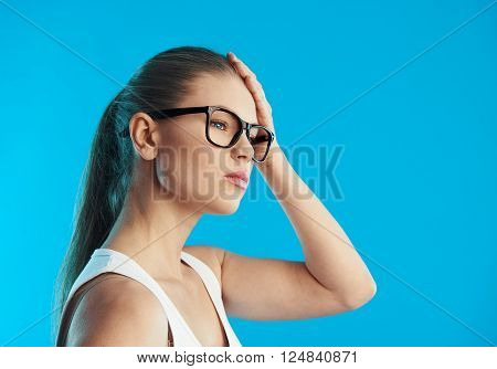 Portrait of young sick female suffering from migraine or vertigo over blue background. Concept of head illness diagnosis and treatment.