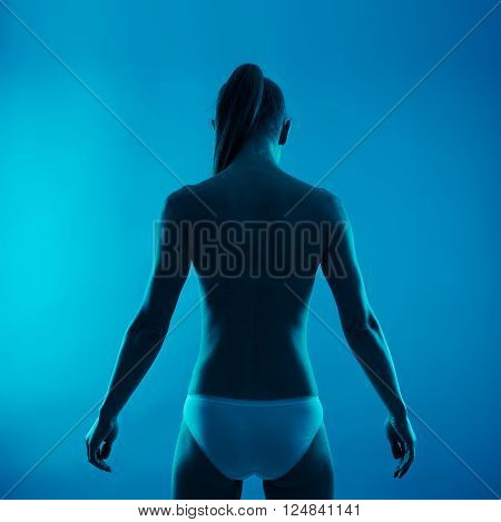 Back treatment and therapy. Shirtless female with healthy spine over blue background.
