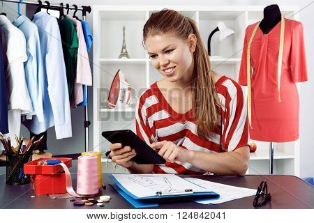 Young woman small atelier owner with tablet blogging in the office. Female dress designer working over sketch in fashion studio.