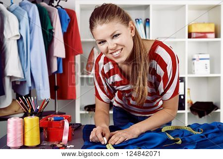 Clothing repair service. Pretty woman measuring textile with tape in workroom. Concept of small business.