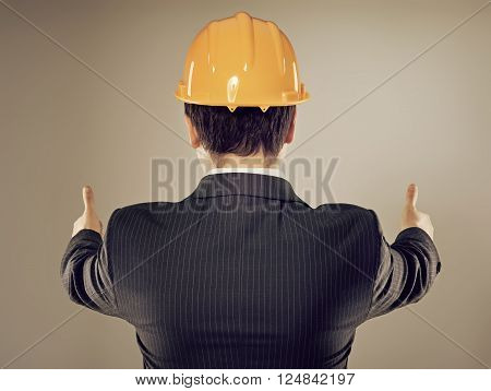 Male engineer in yellow helmet showing thumbs up