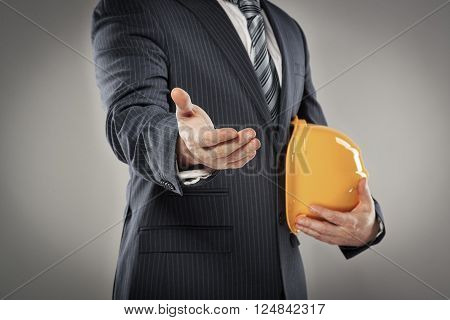 Partnership concept. Businessman with helmet greeting somebody.