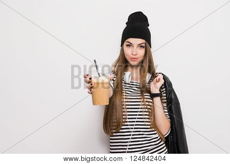Cool urban teenage girl in black and white outfit, holding plastic coffee cup with straw. No retouch, copy space available.