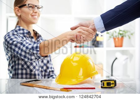 Young female designer shaking hand with male customer in the office. Business agreement of architectural project.