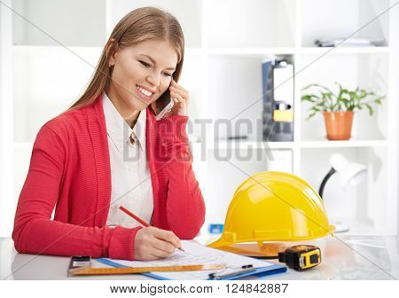 Successful female engineer drawing house draft and talking on phone with customer. Woman multi-tasking.