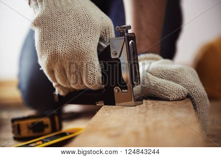 Male installer using stapler for wooden plank. Concept of home improvement.