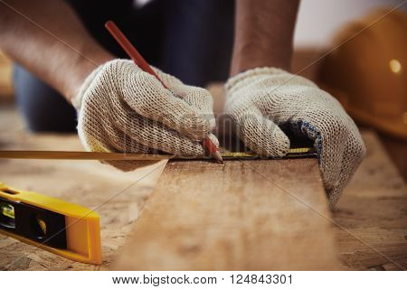 Close-up of male carver's hands measuring wooden balk with tape in workshop.