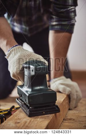 Male carpenter using electric planer for woodwork in joinery. Concept of DIY and furniture renovation.