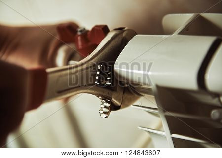 Plumbing repair service. Professional installer with spanner checking pipes.