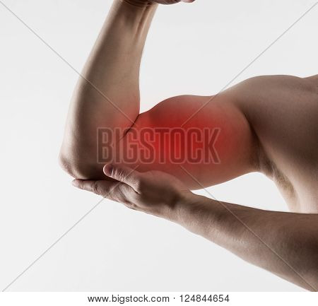 Muscle strain and stretch. Muscular man suffering from sore biceps pain. Concept of health care and medicine.