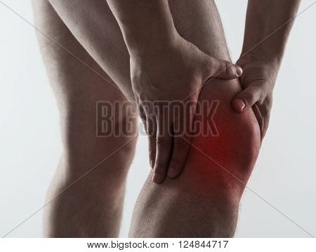 Red spot on painful male knee over light grey background. Man having rheumatism and sprain problem.