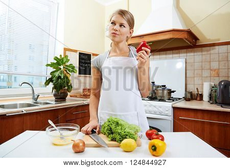 Thoughtful female searching creative idea what to cook. Young pretty woman holding red pepper thinking of preparing new dish.