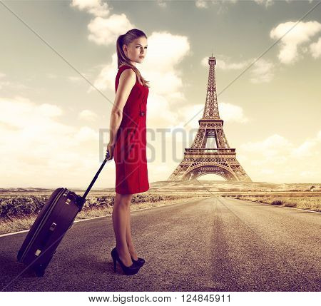 French voyage concept. Pretty elegant lady over beautiful scenic Paris landscape. Young female shopping tourist holding suitcase standing on the road.