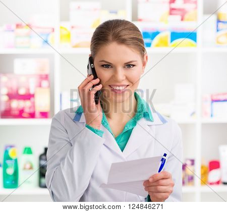 Portrait of attractive woman chemist in uniform talking on phone in drug store. Young female pharmacist reading recipe to customer.