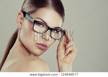 Clear vision concept. Beauty studio portrait of young pretty female wearing stylish eyeglasses with blank space.