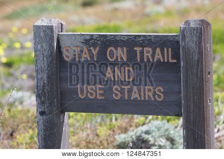 This is an image of an old coastal park trail sign taken on a sunny Spring day.