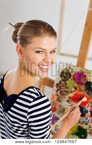 Smiling woman painter with paintbrush standing at easel drawing with acrylic paints. Young pretty girl working in her artistic studio.