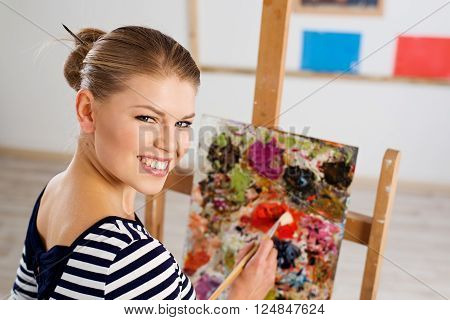 Portrait of young smiling female with paintbrush and palette working in studio. Joyful woman painter creating new picture.