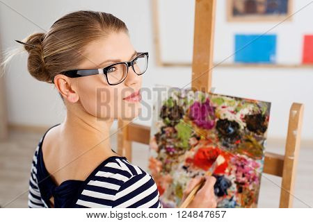 Young female artist with color palette and brush in studio. Attractive woman painter thinking of drawing new picture.