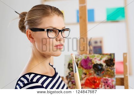 Working woman artist with paintbrush in artistic studio. Young attractive girl painter creating oil picture.