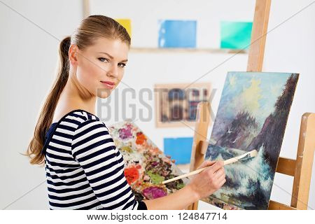 Concentrated student painter standing with color palette and brush at wooden easel. Young artist girl drawing picture in university studio.