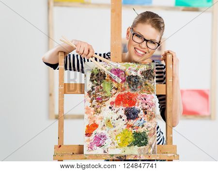 Smiling young female painter standing behind wooden easel with colorful oil palette. Portrait of happy girl artist holding brushes.