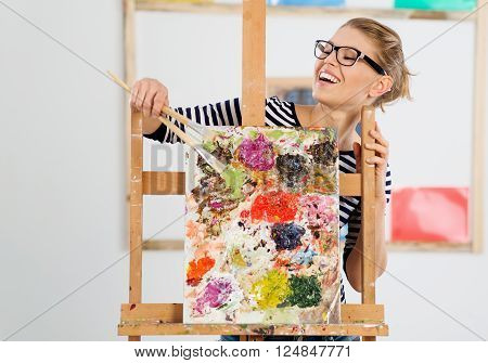 Portrait of laughing female painter showing her colorful artwork. Young lovely woman artist standing behind easel in her studio.