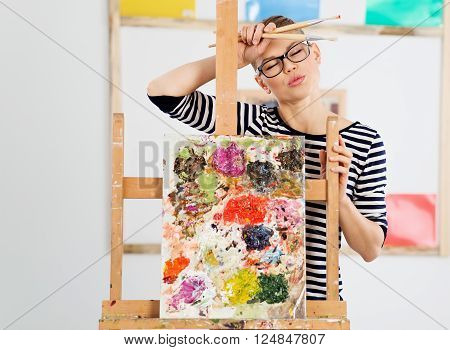 Tired woman artist standing with brushes at canvas in studio. Portrait of female painter weary after working on picture.