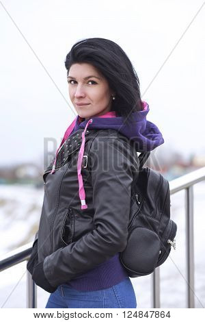 Outdoors A beautiful young brunette woman posing in a black leather jacket with a leather backpack. Autumn cloudy lifestyle. Portrait of a stylish young hipster on the street in the city. Close-up.