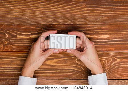 Paper house figure and blank business card on wooden background. Real Estate Concept. Top view.