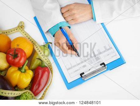 Close-up of doctor dietitian hands with pen prescribing treatment. Female physician filling medical history form in the office.