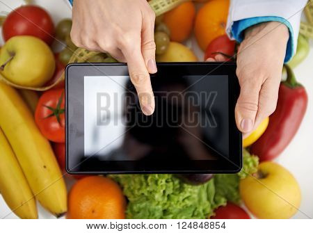 Close-up of doctor nutritionist pointing at smth on digital tablet screen. Weight loss and health care.
