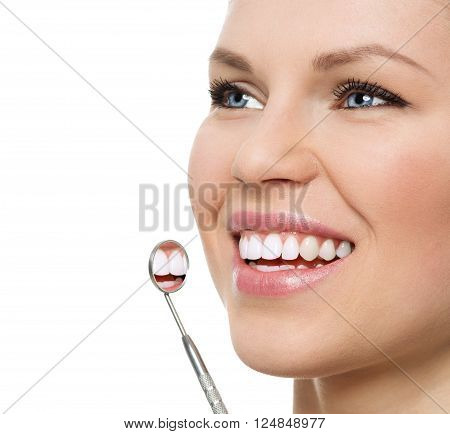 Oral checkup at dentist. Portrait of happy young Caucasian woman with mirror showing her perfect healthy teeth.