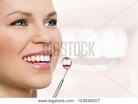 Fresh smile. Teeth whitening. Oral check up. Portrait of young cheerful woman examining her teeth with dental mirror.