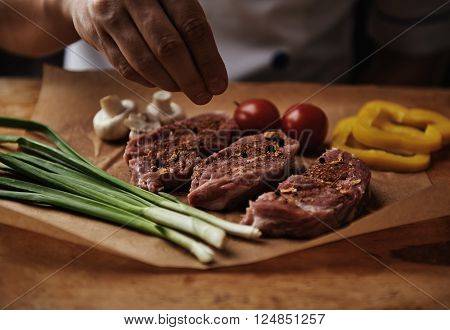 Close-up of chef putting salt on raw beef preparing meat for grill. European food. Meat and vegetables.