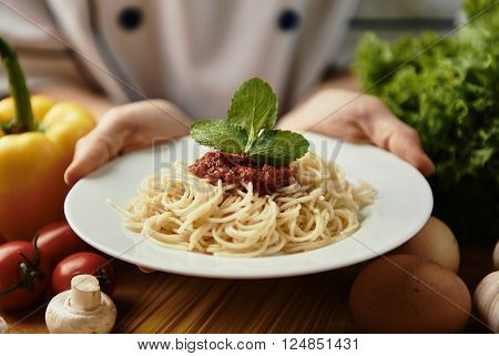 Female cook hands holding plate with spaghetti and vegetable sauce in the kitchen. Delicious garnish serving.