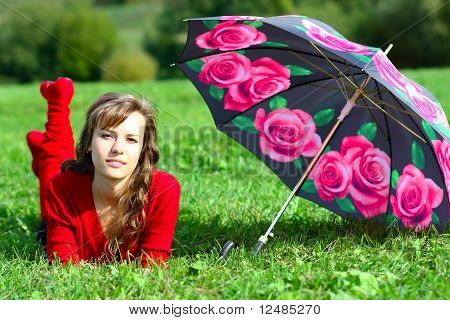 Beautiful Girl In Red Laying On The Lawn In Park