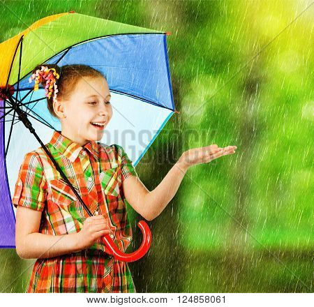 Beautiful fashion girl dressed in bright clothes with a rainbow umbrella in her hand enjoys the rain in a summer park.