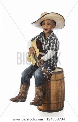 A handsome young African boy happily singing and playing his guitar as he sits on an old barrel.  On a white background.